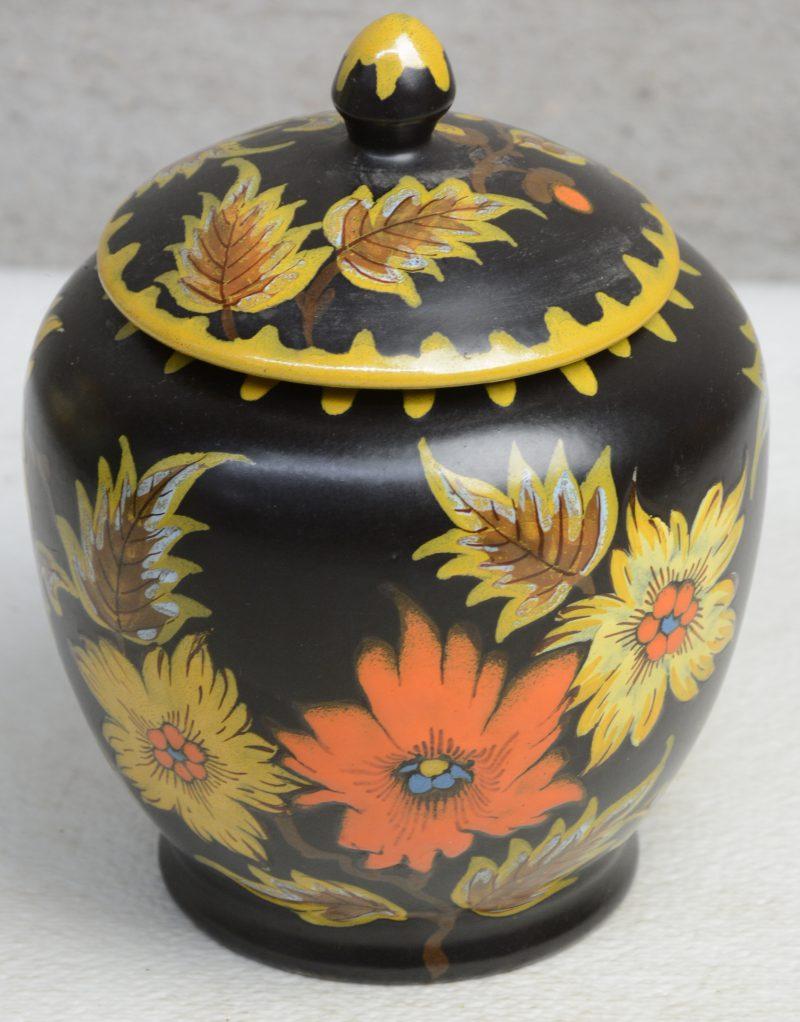 Een tabakspot van zwart plateel met een meerkleurig bloemendecor 'Mekka'. Onderaan gemerkt.