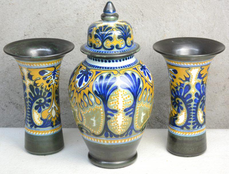Een driedelig kaststel van meerkleurig Gouds plateel, bestaande uit een dekselvaas en twee hoornvazen. Decor 'Cyprus'. Onderaan gemerkt.