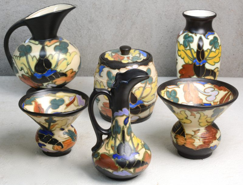 Een lot meerkleurig aardewerk in de stijl van Gouda, bestaande uit twee kwispedoors, een vaas, twee kannen en een tabakspot.