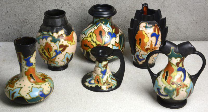 Een lot meerkleurig Gouds plateel, bestaande uit vijf verschillende vazen en een kandelaar. Onderaan gemerkt.