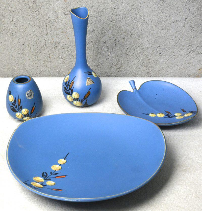 Een lot Gouds aardewerk bestaande uit een schotel, een bladvormig schaaltje (restauratie) en twee vaasjes. Gemerkt.