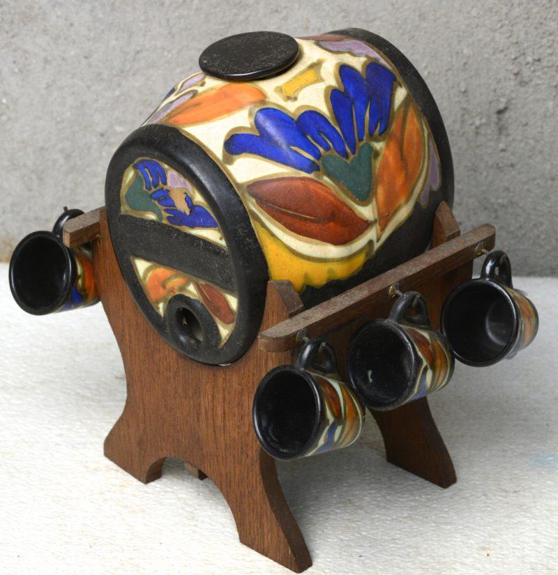 Een jenevervaatje van meerkleurig aardewerk in de stijl van Gouda. Op staander en met zes borreltjes. Zonder kraantje.