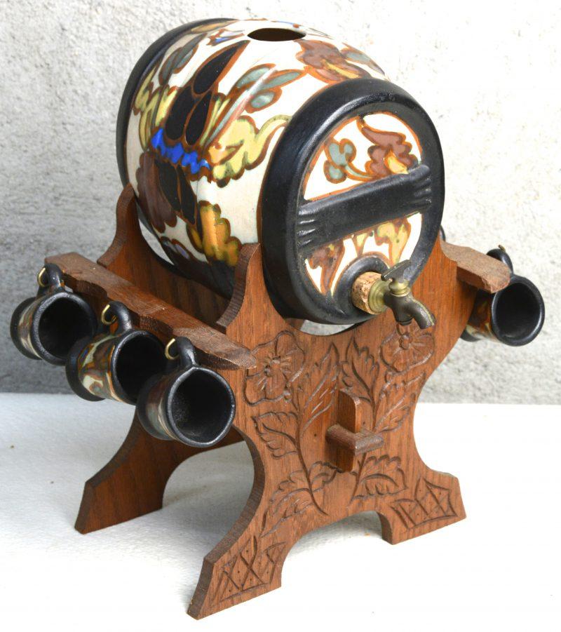 Een jenevervaatje van meerkleurig aardewerk in de stijl van Gouda. Op staander en met zes borreltjes.