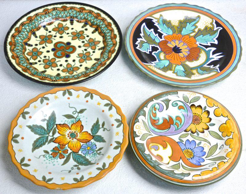 Een lot van vier verschillende schotels van meerkleurig plateel met decors 'Corfoe', 'Wally', 'Vola' & 'Magda'. Onderaan gemerkt.
