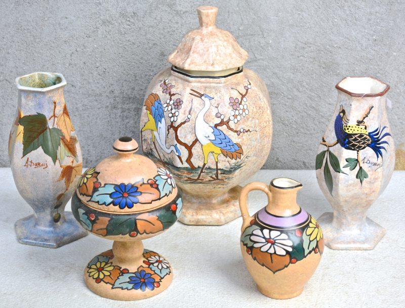 Een lot meerkleurig aardewerk, bestaande uit een bonbonnière op voet, een kruikje (restauraties), twee zeshoekige vazen (één gerestaureerd) en een dekselvaas, versierd met decors van A. Dubois.