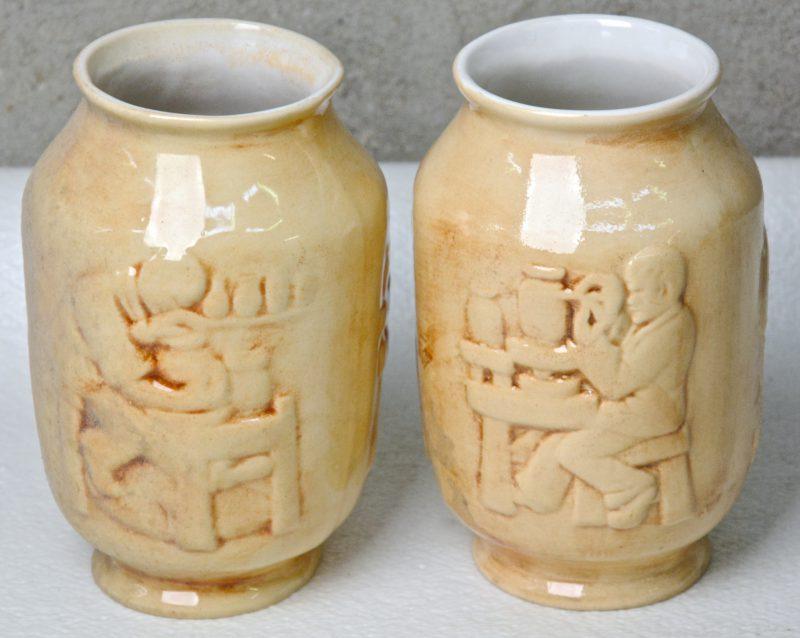 Twee bruingeglazuurde aardewerken vaasjes met een reliëfdecor van pottebakkerijtaferelen. Onderaan gemerkt. Gaaf.