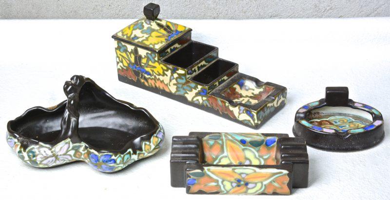 Een rokersstel, twee asbakken en een mandje van meerkleurig aardewerk in de stijl van Gouda. Onderaan gemerkt.