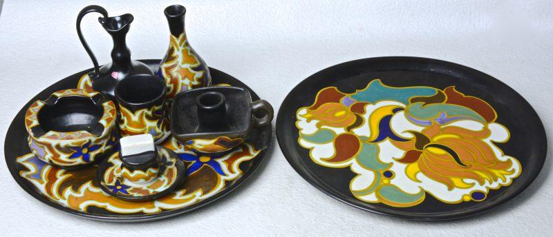 Een lot meerkleurig plateel, bestaande uit een vaasje (restauratie) en een driedelig rokersstelletje (asbak gerestaureerd) op schotel met decor 'Herfst', een ronde schotel met decor 'Ruby', een blaker met decor 'Daisy' en een zwart kannetje (schilfer onderaan).
