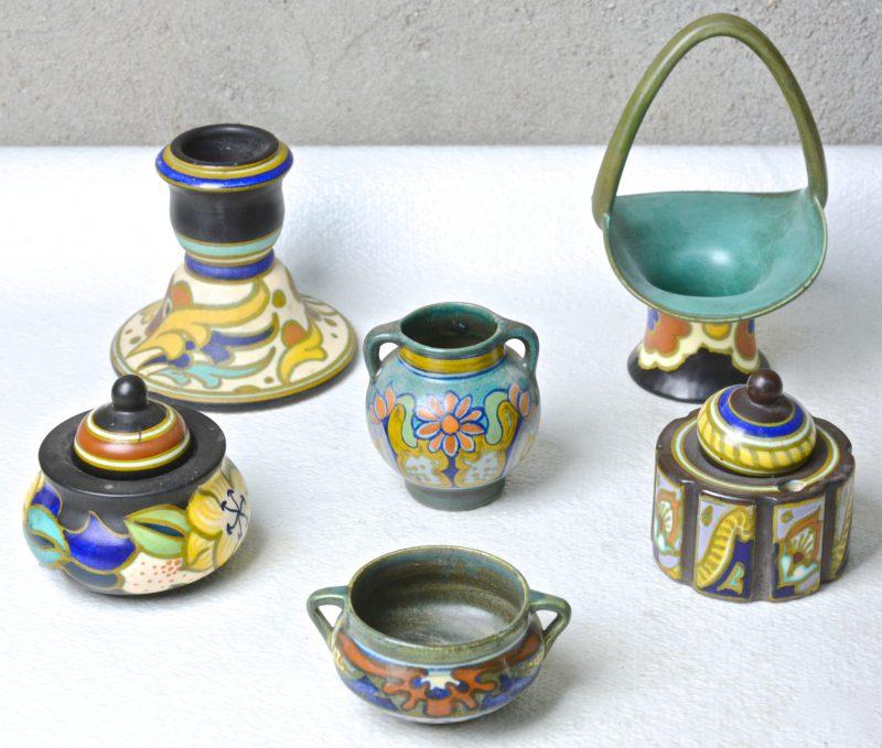 Twee inktpotten (Eén deksel gerestraureerd), een kandelaar, een mandje en twee vaasjes van meerkleurig Gouds aardewerk. Grotendeels Plazuid.