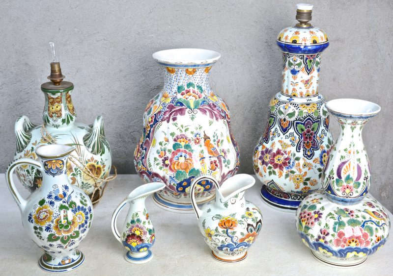 Een lot Holands plateel met meerkleurige Delftse decors, bestaande uit twee lampvoeten, drie kannetjes (één met haarscheur) en een knobbelvaas. Diverse merken, waaronder 'RAM'.