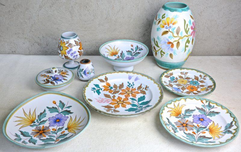 Een lot Gouds plateel met meerkleurig decor van bloemen en bladeren, bestaande uit een kleine en een grote vaas, een vaasje op voet, vier schotels, een kom op voet en een bonbonnière. Onderaan gemerkt.