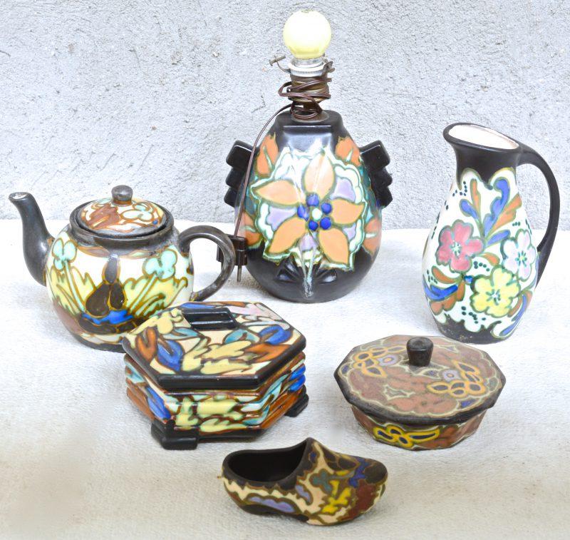 Een lot meerkleurig aardewerk in de stijl van Gouda, bestaande uit een theepot, twee dekseldozen, een lampvoet, een klompje en een kan. Gemerkt.