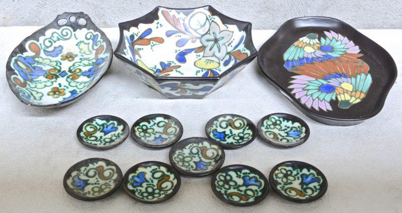 Een schaal met negen bordjes, een schotel en een achthoekige fruitschaal van meerkleurig aardewerk in de stijl van Gouda. Onderaan gemerkt.