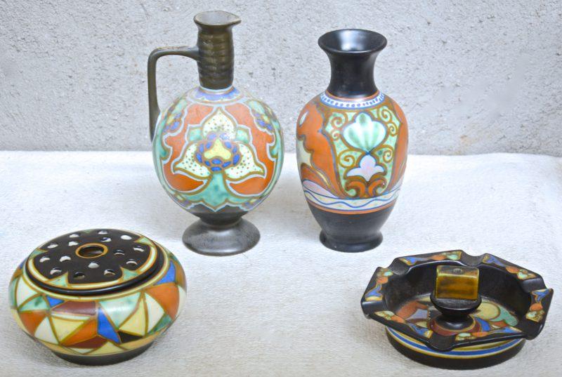 Een lot meerkleurig aardewerk met Goudse decors, bestaande uit een pique-fleurs, een kruik, een vaasje en een asbak. Onderaan gemerkt.