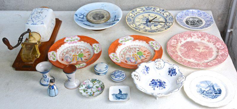 Een gevarieerd lot aardewerk van diverse oorsprongen, bestaande uit borden, doosjes, klokken, een koffiemolen, enz.