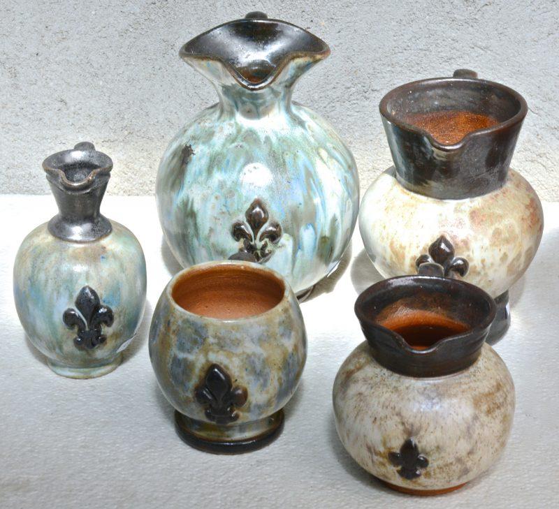 Vijf kannetjes van geglazuurd steengoed, versierd met een Franse lelie. Onderaan gemerkt.