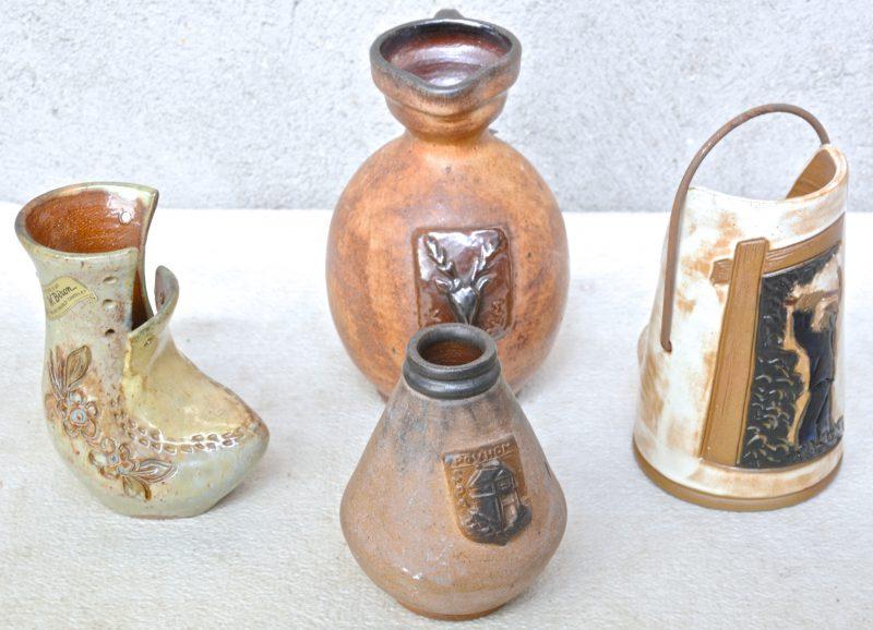 Een lot steengoed, bestaande uit een vaasje met een wapen van 'Pouhon - Spa', een kruikje met 'Vielsalm', een sieremmertje met een mijnwerker en een siervaasje met bloemendecor. Onderaan gemerkt.