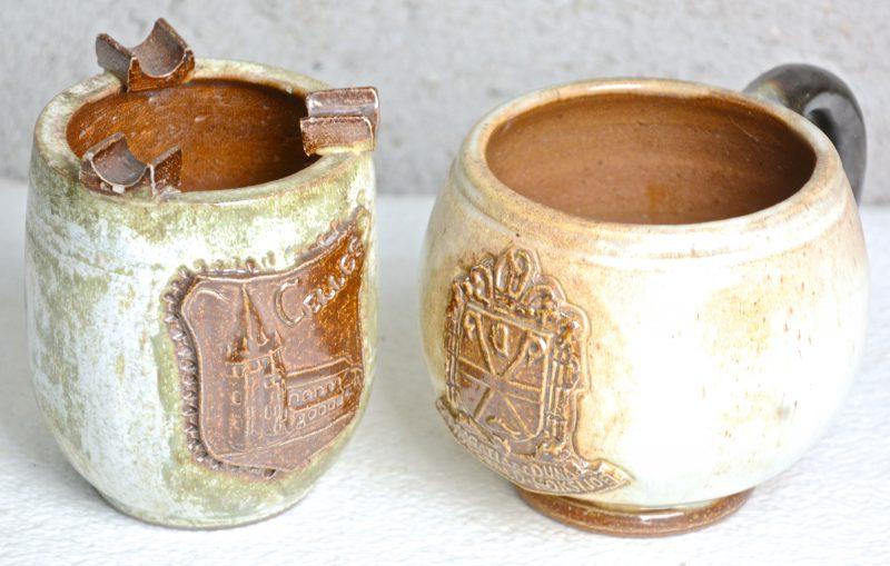 Een asbak en een pul van steengoed, respectievelijk met een wapen van Celles en van St. Idesbald - Koksijde. Onderaan gemerkt.
