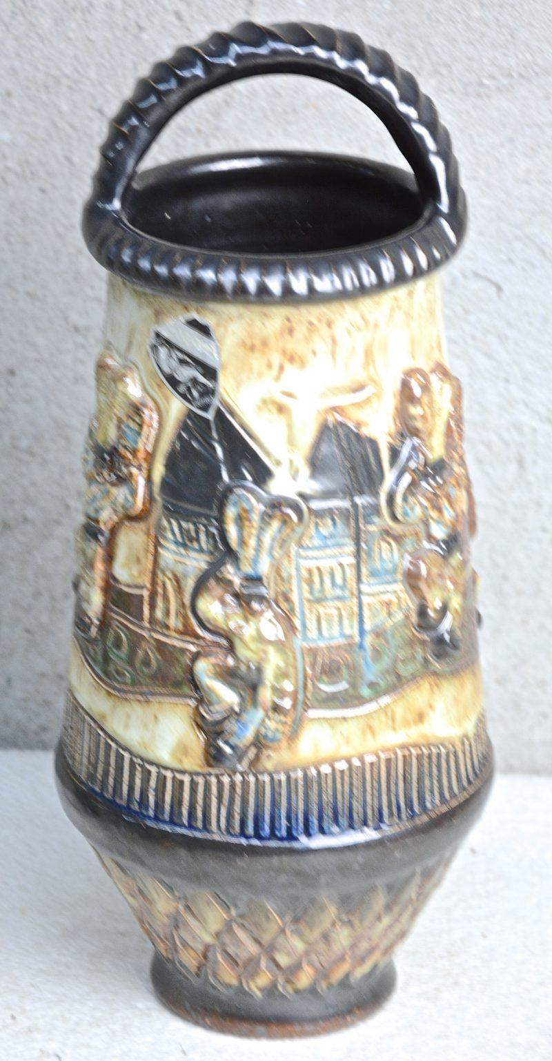 Een siervaas van meerkleurig geglazuurd steengoed met een carnavalsscène in reliëf. Gemerkt.