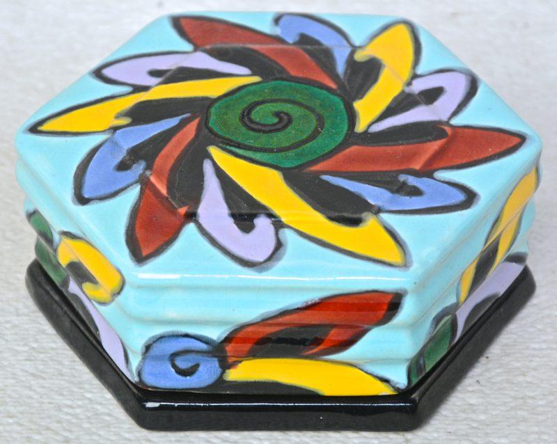 Een zeshoekig art deco dekseldoosje van aardewerk met een meerkleurig decor. Onderaan gemerkt. Schilfer aan de binnenkant.