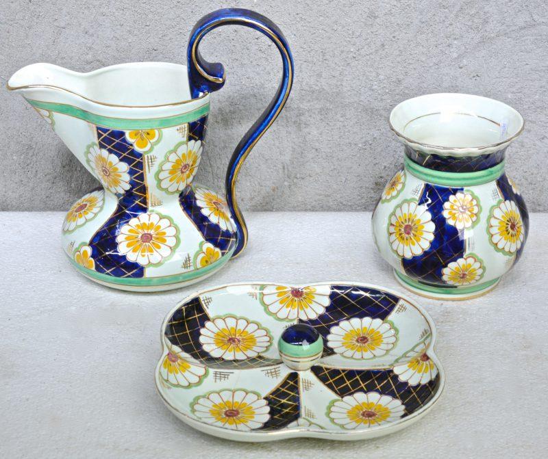 Een schenkkan, een vaas en een aperitefschotel van meerkleurig aardewerk, versierd met decor 'Sinia'.