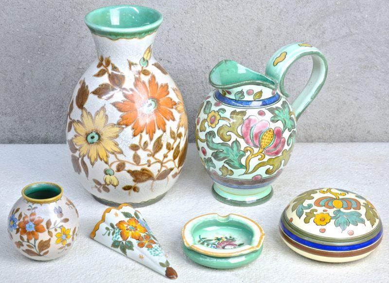 Een lot Gouds plateel met meerkleurige bloemendecors, bestaande uit een wandvaasje, een dekseldoos, een asbak, een grote en een kleine vaas en een kan. Onderaan gemerkt.