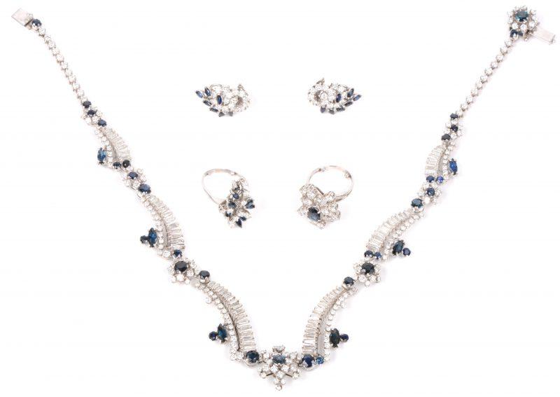 Een 18 karaats witgouden parure waaronder een halssnoer met bijpassende oorbellen en twee ringen bezet met diamanten en baguetten met een gezamenlijk gewicht van ± 14 ct. en saffieren met een gezamenlijk gewicht van ± 7 ct.