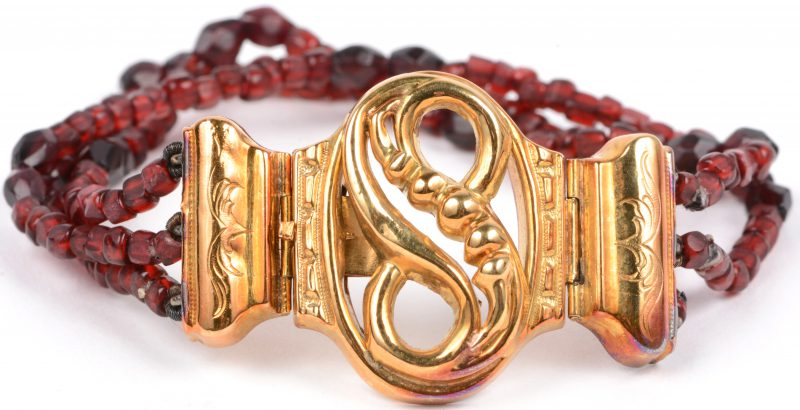 Een 18 karaats geel gouden armband bezet met granaat kralen.