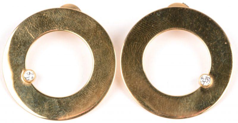 Een paar 18 karaats geel gouden oorbellen bezet met twee briljanten met een gezamenlijk gewicht van ± 0,20 ct.