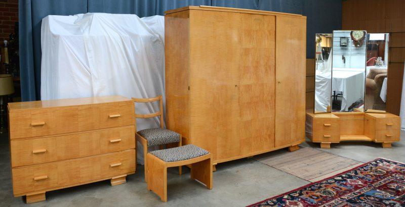 Een berkenhouten slaapkamer, bestaande uit een grote garderobe, een bed met twee, aan de sponde bevestigde nachtkastjes, een kaptafel en een commode met drie laden.