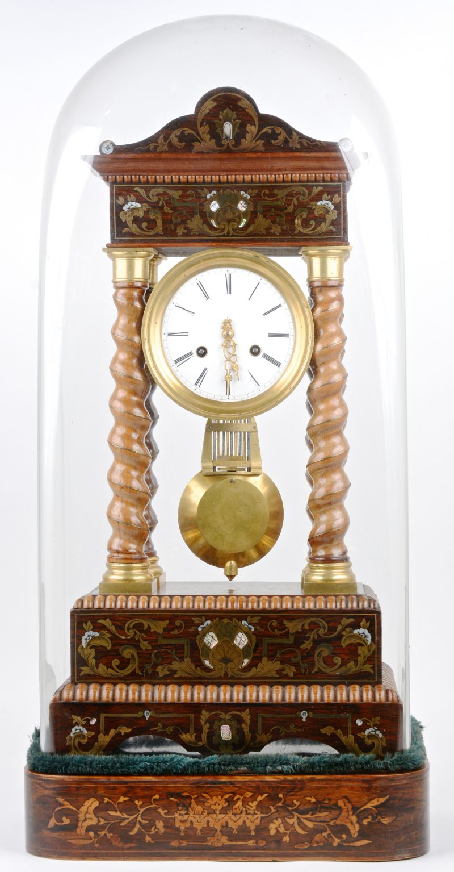 Een Napoleon III kolompendule, versierd met inlegwerk van messing en parelmoer. Onder stolp met eveneens gemarquetteerde voet. Met sleutel.