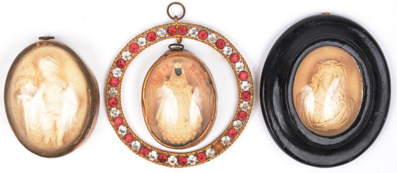 Drie XIXe eeuwse religieuze reliëfjes van pijpaarde achter glas.