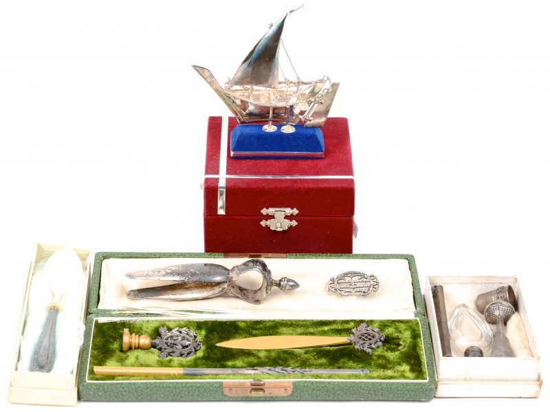 Een lot zilver en verzilverd metaal, bestaande uit een zeilbootje, een lepeltje met ivoor, een suikertang, een potloodhoudertje, een broche, een ruikflesje, een vingerhoed, een stempel en een driedelig schrijfsetje in etui.