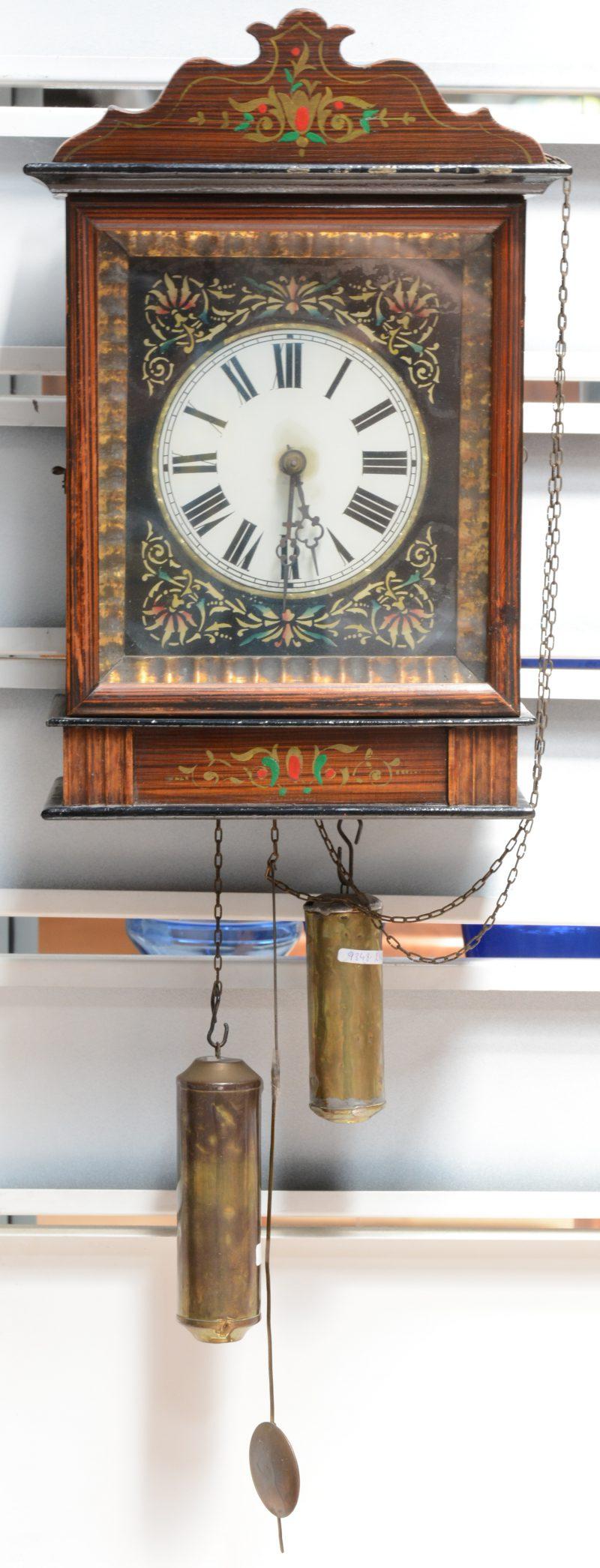 Een houten wandklok met een églomisé wijzerplaat met versieringen.