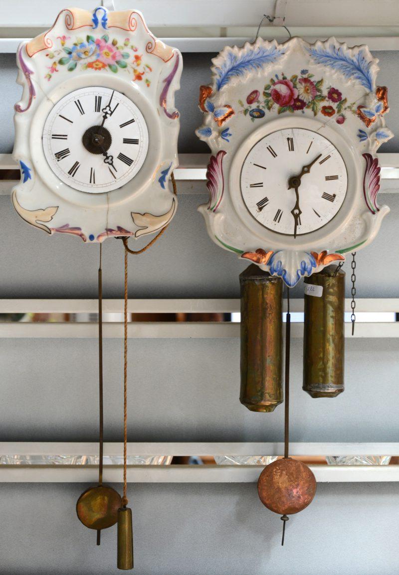 Twee wandklokjes  met handbeschilderde porseleinen wijzerplaat. Enkele barsten en één van de twee zonder gewichten.