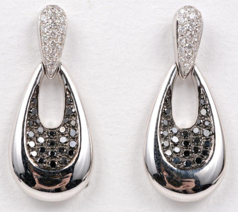 Een paar 18 karaats wit gouden oorbellen bezet met witte en zwarte diamanten met een gezamenlijk gewicht van ± 0,52 ct.
