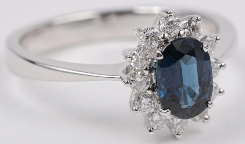 Een 18 karaats wit gouden ring bezet met briljanten met een gezamenlijk gewicht van ± 0,28 ct. en een centrale saffier van ± 0,93 ct.