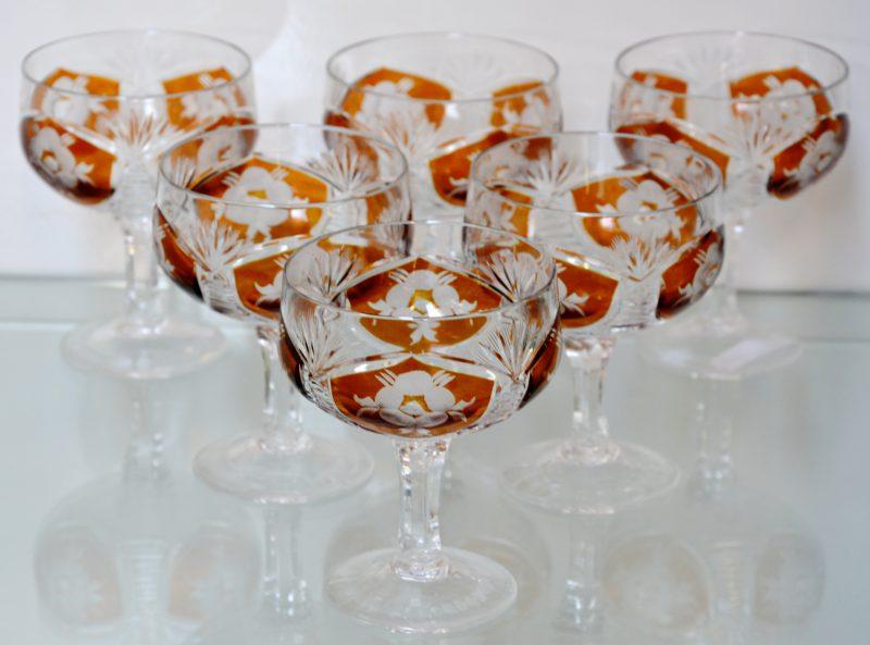 Een lot van zes geslepen en gegraveerde kristallen glazen, oranje in de massa, met bloemdecor.