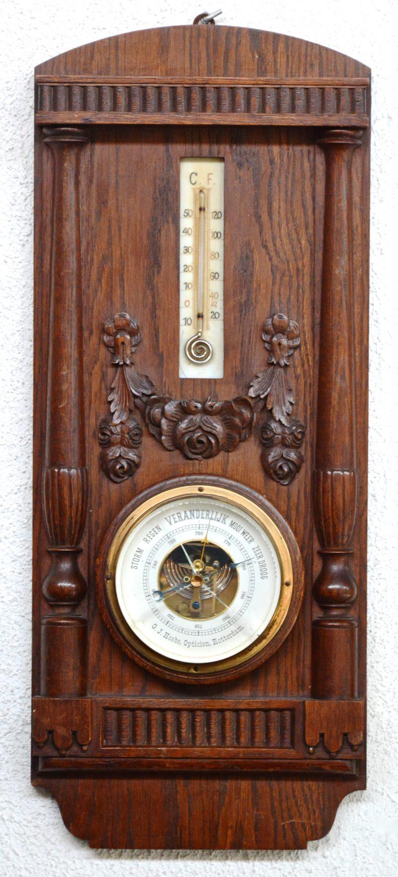 Een eikenhouten barometer-thermometer met gesculpteerde versieringen. Glas gebarsten.