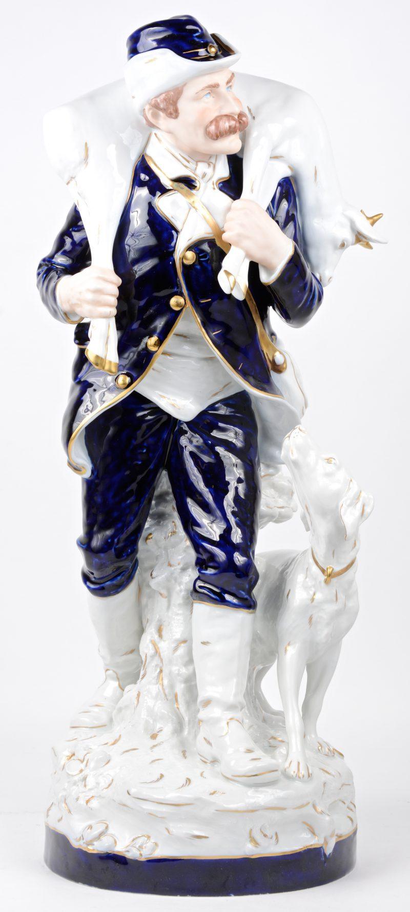 """""""Jager met zijn hond en hun buit"""". Een beeld van blauw-wit en verguld porselein. Onderaan gemerkt. Stukje gewei afgebroken."""