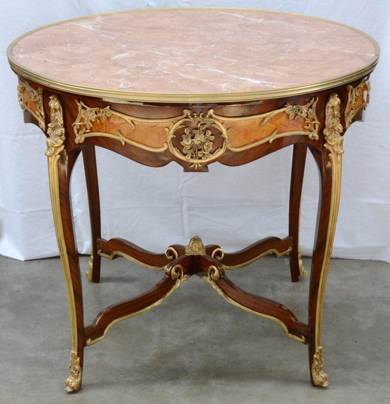 Een ronde tafel met roze marmeren blad in louis XV stijl.
