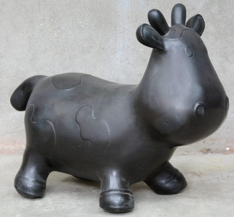 Een cartooneske koe van  zwartgelakt metaal.