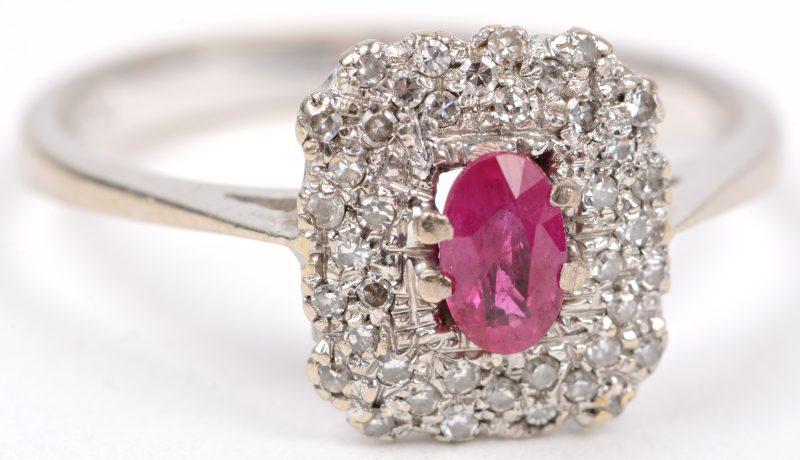 Een 18 karaats wit gouden ring bezet met briljanten met een gezamenlijk gewicht van ± 0,20 ct. en een centrale robijn van ± 0,20 ct.