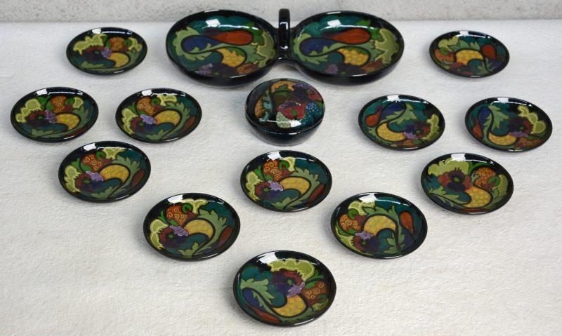 Een dubbel aperitiefschaaltje, twaalf kleine bordjes en een dekseldoosje van Gouds aardewerk, versierd met een meerkleurig decor met hoogglanzend glazuur. Begin XXe eeuw. Onderaan gemerkt.