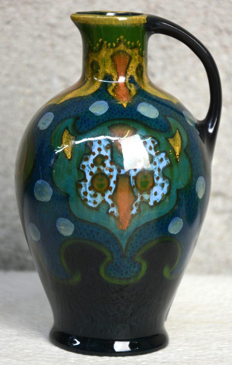 Een art nouveau kruikje van Gouds aardewerk met hooglansglazuur, versierd met een meerkleurig decor, gemonogrameerd 'JK'. Vroeg XXe eeuws. Onderaan gemerkt.