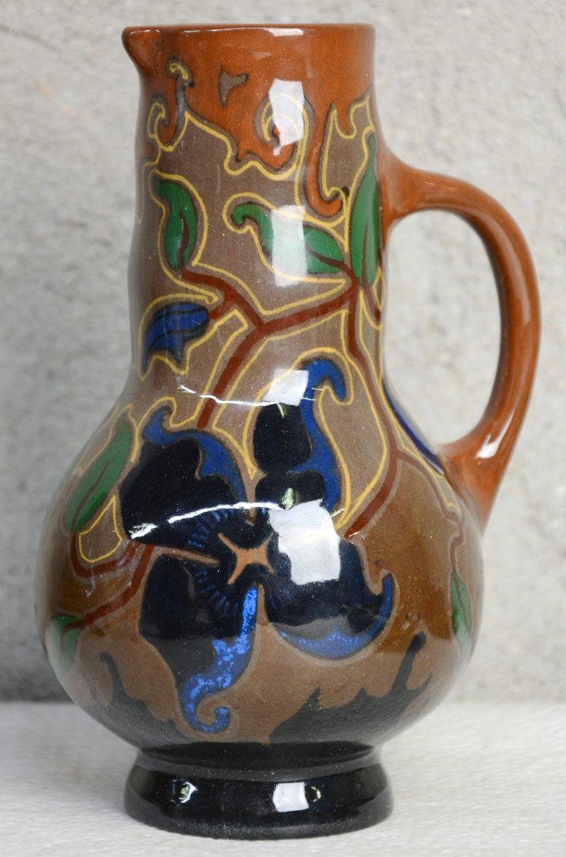 Een kruikje van glansplateel met een meerkleurig bloemendecor. Onderaan gemerkt. Eerste helft XXe eeuw.