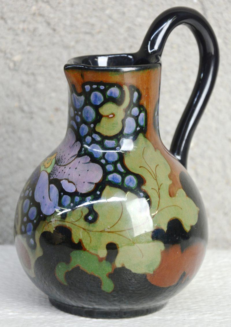 Een klein kannetje van glansplateel, versierd met een meerkleurig bloemendecor. Decorateursmonogram 'MDB'. Onderaan gemerkt.