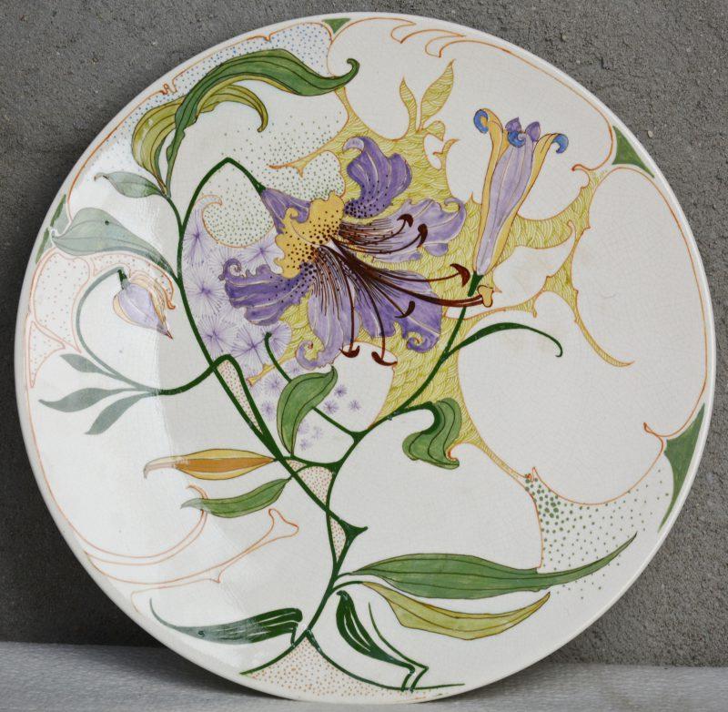 Een art nouveau schotel van Gouds glansplateel, versierd met een meerkleurig bloemendecor. Decorateursmonogram 'RR'. Onderaan gemerkt.