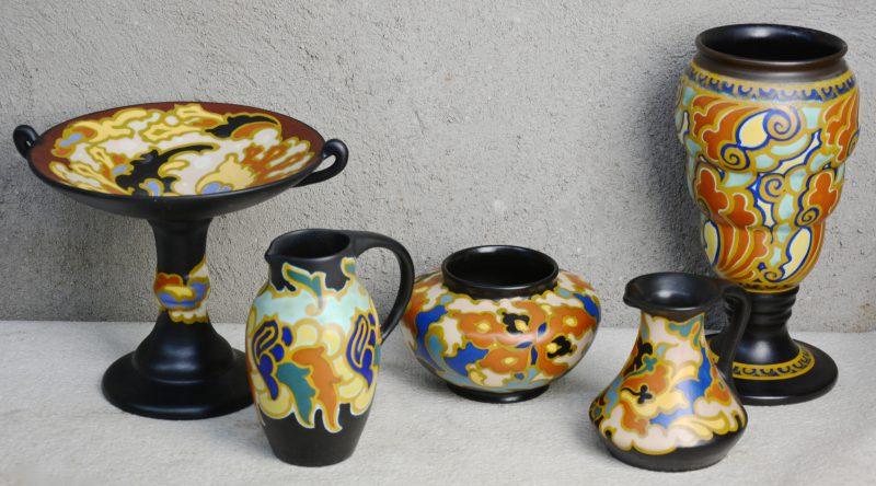 Een lot meerkleurig plateel, bestaande uit een lage vaas, een vaas op voet, een tazza en twee verschillende schenkkannetjes. Verschillende decors. Allen gemerkt onderaan.
