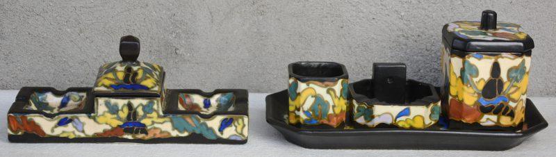 Een driedelig rokersstelletje op dienblaadje en een dubbele asbak met deksel van meerkleurig aardewerk. Onderaan gemerkt. Deksel van het tweede met haarscheur.